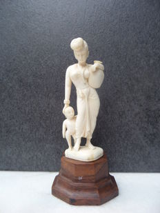 Ivory sculpture of a women with shild; on wooden stand - India - around 1930