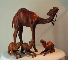 Four leather camel statues