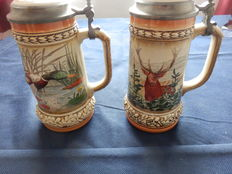 2 Richly decorated beer mugs with hunting motif in relief