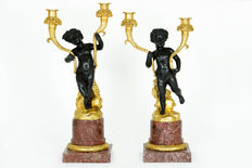 Set of 2 large bronze empire style candlesticks decorated with putti -on marble pedestals - well over 7 kg each