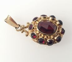 Yellow gold pendant (4.2 cm x 0.81 x 0.62 cm) with 11 faceted cut garnets