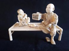 Finely carved ivory okimono of a man and child on a bench - Japen -  ca . 1900