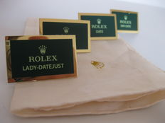 """4 Rolex exclusive nameplate display stands for the models: """"Datejust"""", """"Day-date"""", """"Date"""" and """"New"""", with beige cotton handkerchief."""