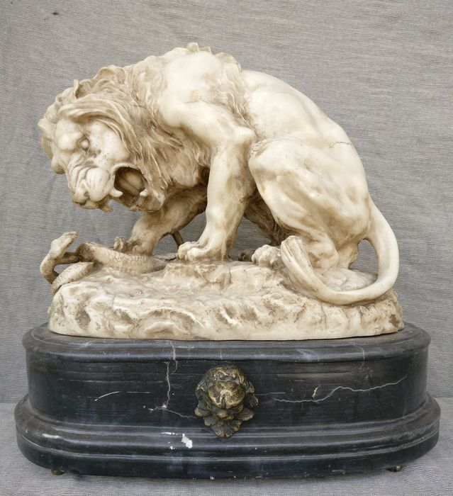 """Lion fighting a snake"", sculpture in marble dust, on a Portoro black marble base - France, early 20th century"