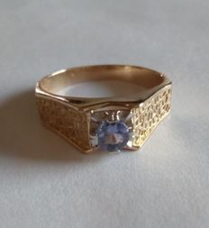 Two-tone gold solitaire ring set with a central tanzanite gemstone measuring: 5 mm.
