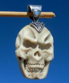 Ethnic skull pendant, carved from bone, adorned with opal - 39 mm