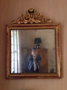 Great mirror of Italian style very detailed on the top, frame covered in gold leaf.