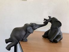 2 handmade statues of an elephant in distress.