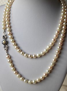 Very long 90 cm, Akoya necklace with genuine  sea/salty, white pearls AA, with lustre,  from the Japanese sea on 14 kt white gold, antique clasp set with twelve blue sapphires.