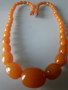 Necklace composed of old natural Baltic amber polished beads in orange-yellow colour. Weight: 31 g.
