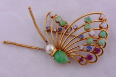Vintage butterfly-shaped gold brooch, with jade, moonstone, diamonds, rubies and emeralds.