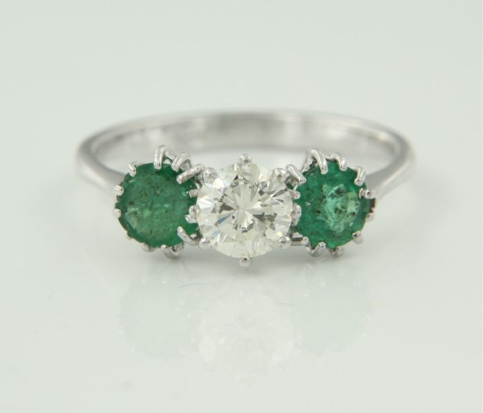 18 kt white gold trilogy ring set in the centre with a 0.60 ct brilliant cut diamond and two brilliant cut emeralds, 1.20 ct, ring size 17.25 (54)