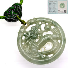 Green jade pendent engraved with the shape of a dragon. Jadeite type A.