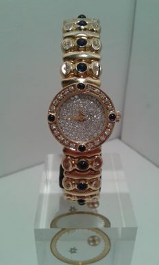 Bracelet in 18 kt gold with quartz watch, diamonds and sapphires.