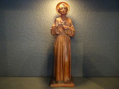 Wood-carved statue of a saint with rosary and crucifix