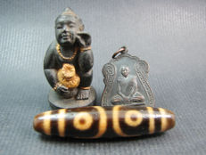 A large heirloom bead with 2 Buddhist amulets - Thailand and Himalayas - 1972 and second half of the 20th century.