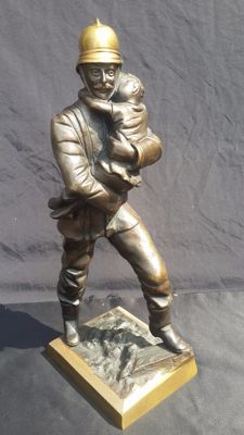 Bronze sculpture of a firefighter holding a rescued child, - Italy, ca. 1900-1919