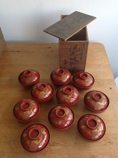 Beautiful, complete set of 10 Owan lacquered wooden bowls & covers, decorated with floral patterns, in the original wooden storage case – Japan – 1900