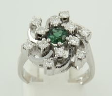 White 14 kt gold ring, set with a central, green tourmaline and 12 brilliant cut diamonds of approx. 0.60 ct in total, ring size: 17 (53).***NO RESERVE PRICE***