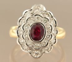18 kt bi-colour gold entourage ring, set with a central, oval cut ruby and 22 brilliant cut diamonds, ring size 17.5 (55).
