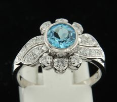 14 kt white gold ring set with centrally an old Amsterdam cut blue topaz and an entourage of 20 old Amsterdam cut diamonds of in total ca. 0.60 ct. Ring size 17.5 (55).