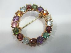 Gold brooch with precious stones.