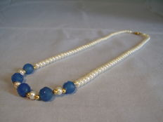White cultivated peal necklace with gold accents and facetted blue chalcedony beads