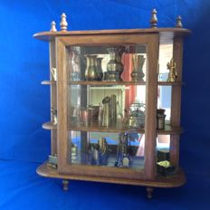 Oak display case cabinet with mirror and glass door, filled with brass miniatures.