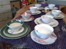Lot of single cups with saucers, each cup is different and with a different decoration