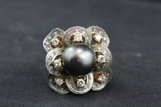 Ring – Gold, black pearl, and diamonds totalling 0.60 ct – Measures 17 mm.