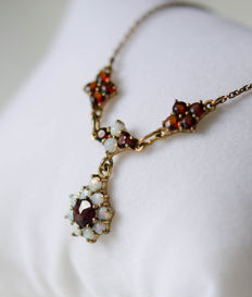A silver necklace with garnets and opals, gold-plated