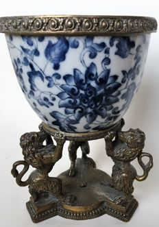 Blue floral porcelain flower bowl with bronze ornamental edge carried by bronze lions on base with pearl edge.