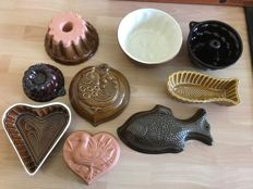 Nine decorative pudding forms with brown glaze