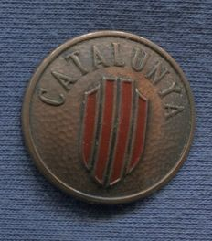 Round metal breast badge. With the text Catalunya. Catalan Volunteers in the Macia-Companys Column and other Catalan Units in the Spanish Civil War.