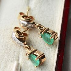 Yellow gold 585/14kt. Earrings, each with teardrop-shaped natural Emerald and small diamonds in white gold.