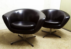 Two lounge chairs – in black skai leather with aluminium leg piece