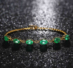 6.5 carat emerald gem, diamonds, 18K gold bracelet.