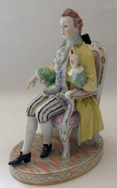 A hand-painted porcelain sculpture of a seated gentleman