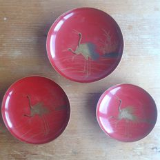 A trio of red wooden lacquered Sakazuki sake bowls with crane design - Japan - around 1910