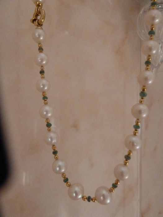 Necklace made of cultured pearls measuring 8-9 mm in diameter, with gold spacers and faceted emeralds measuring 2 mm. Length: 45 cm