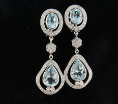 14 kt white gold dangle earrings set with 4 blue topazes of 6.20 ct and 102 brilliant cut diamonds of 0.88 ct, height 4.1 cm, width1.4 cm