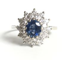 Grey gold (18 kt) daisy ring with a bright Ceylon sapphire (1 ct) in the centre in a double entourage of H/VVS diamonds (1 ct).