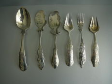 6 Pieces of silver serving cutlery consisting of: 1 Serving spoon, 2 pastry servers, 2 ginger forks, 1 serving fork, ornately engraved, 2nd half of 19th century, The Netherlands.