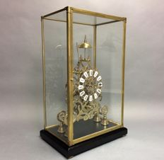 Skeleton clock underneath glass case with striking mechanism and fusee movement - mid 20th century