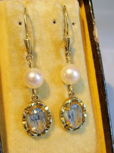 Gold earrings with light blue spinels and white Akoya pearls.