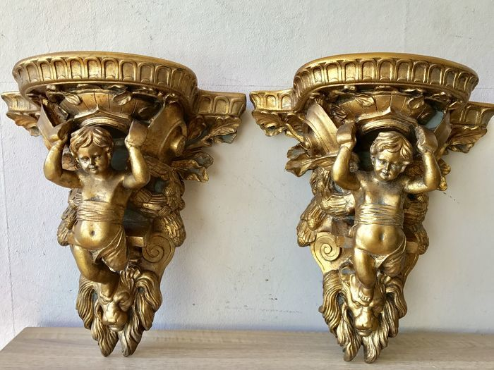 Two large gold-plated baroque style wall consoles with angels