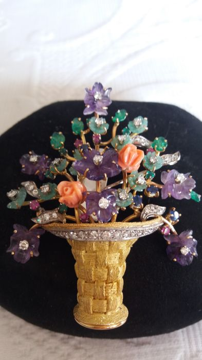 Stylised gold brooch in the shape of a vase with branches, petals and flower buds, with precious stones
