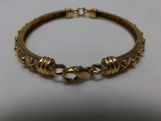 Hinged 18 kt gold bracelet with artisan design.