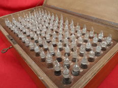 Unique lockable wooden box from a laboratory with 98 small lidded bottles, complete set.
