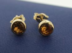 Gold solitaire earrings of 14 kt, inlaid with citrine. Length: 1 cm. Width: 0.5 cm